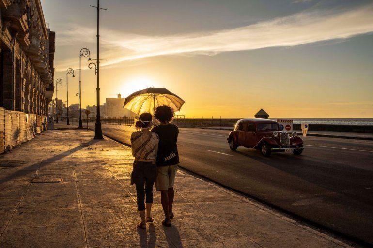 Una pareja con mascarillas para protegerse del nuevo coronavirus sostiene un paraguas mientras camina por el malecón al atardecer en La Habana