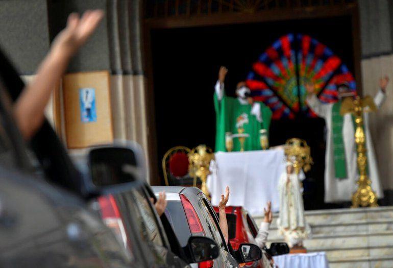 Feligreses asisten a una misa dominical en autocine montada por el padre Jonathan González para eludir las normas que impiden las concentraciones en los templos religiosos