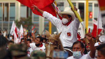 El candidato presidencial peruano por el partido de izquierda radical Perú Libre (Perú Libre), Pedro Castillo, monta un caballo sosteniendo un lápiz gigante durante el mitin de clausura de su campaña en Lima el 8 de abril de 2021.