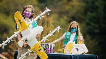 Foto provista por la empresa Wing LLC. En ella se ve a las Girl Scouts Alice Goerlich y Gracie Walker posando con un dron para entregar las galletas que venden en Christiansburg, Virginia.