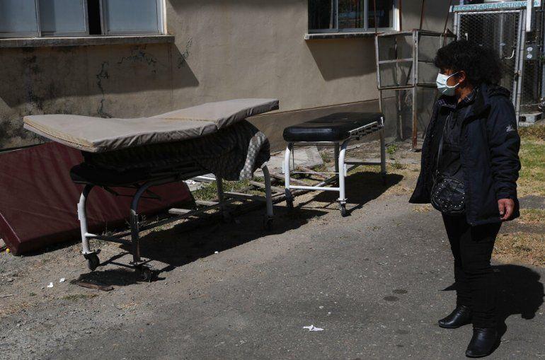 Herminia Carpio mira el cuerpo de su hermano Guillermo cubierto por un delgado colchón afuera del Hospital General antes de que su cuerpo sea llevado por una funeraria en La Paz