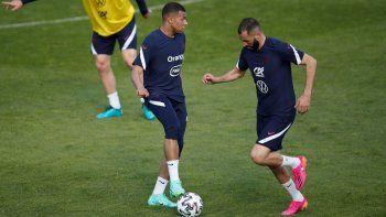 Kylian Mbappé, a la izquierda, y Karim Benzema asisten a una sesión de entrenamiento de la selección francesa de fútbol en el centro de entrenamiento de Clairefontaine, en las afueras de París, el domingo 30 de mayo de 2021.