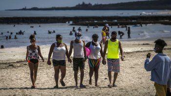 Personas que usan máscaras como precaución contra la propagación del nuevo coronavirus caminan en la playa en La Habana, Cuba, el domingo 11 de octubre de 2020.