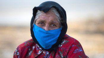 Una mujer mayor usa una mascarilla facial como medida preventiva contra la propagación del COVID-19 en Managua, el 16 de abril de 2020, un día después de que el dictador Daniel Ortega hablara de la pandemia de coronavirus y anunciara que no habría cuarentena o cese de la actividad económica en el país.
