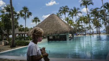 Con una máscara contra la propagación del nuevo coronavirus, una turista camina por el área de la piscina del hotel Meliá Habana en La Habana, Cuba, el jueves 11 de febrero de 2021.
