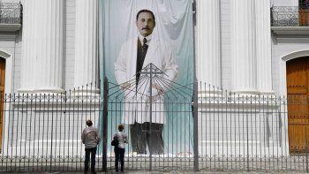 En esta foto de archivo tomada el 21 de junio de 2020, la gente observa la imagen del médico venezolano José Gregorio Hernández, en la parte exterior de la iglesia La Candelaria, que guarda sus restos, en Caracas.
