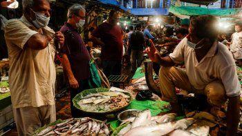 Varias personas usan mascarillas para protegerse del coronavirus el sábado 22 de agosto de 2020 mientras compran pescado en un mercado, en Kolkata, India.