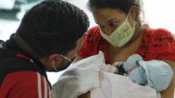 Ada Mendoza muestra su hija a su pareja Leo Camejo por primera vez, horas después de dar a luz en el Hospital Público de Maternidad y Niños Hugo Chávez Frías, en el barrio El Valle de Caracas, Venezuela.