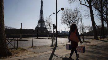 Una mujer camina en una calle vacía cerca de la Torre Eiffel durante un confinamiento a nivel nacional para frenar la propagación del nuevo coronavirus, en París, el jueves 26 de marzo de 2020.