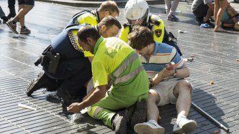 Una persona es ayudada por policías españoles y dos hombres después de que una camioneta se estrellara contra la multitud en Las Ramblas de Barcelona en 2017.
