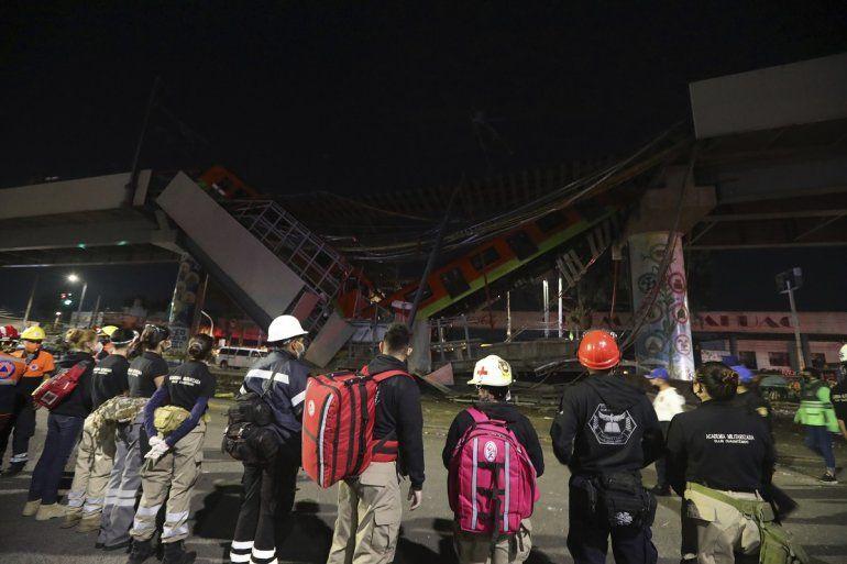 El personal de rescate se detiene frente a los vagones del metro de Ciudad de México después de que una sección de la Línea 12 se derrumbó en la capital mexicana
