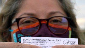 Alejandra, una dentista mexicana y que pidió no revelar su apellido, posa con su tarjeta de vacunación después de recibir la segunda dosis de la vacuna de Moderna contra el COVID-19, el lunes 19 de abril de 2021, en Pasadena, Texas. Alejandra, quien vive en Monterrey, México, dijo que decidió vacunarse en EEUU poco después de perder a su madre por COVID-19 en febrero.