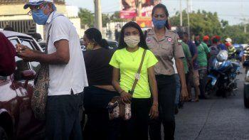 Las personas usan máscaras faciales mientras caminan por una calle de Maracaibo, estado de Zulia, Venezuela, el 2 de julio de 2020, en medio de la pandemia del coronavirus COVID-19.