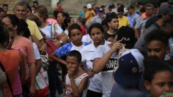 Migrantes de distintos países, incluyendo Honduras, Cuba, Venezuela y Nicaragua, hacen fila para recibir alimentos donados por voluntarios de Estados Unidos, al pie de un puente que cruza a Brownsville, Texas, en el centro de Matamoros, en el estado de Tamaulipas, México.