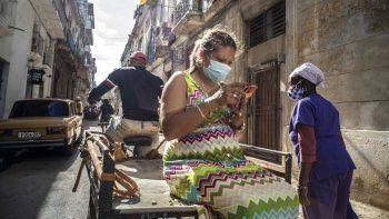 Una mujer que usa una máscara para frenar la propagación del nuevo coronavirus mira su teléfono móvil mientras viaja en un carrito de bicicleta en La Habana, Cuba, el miércoles 23 de diciembre de 2020