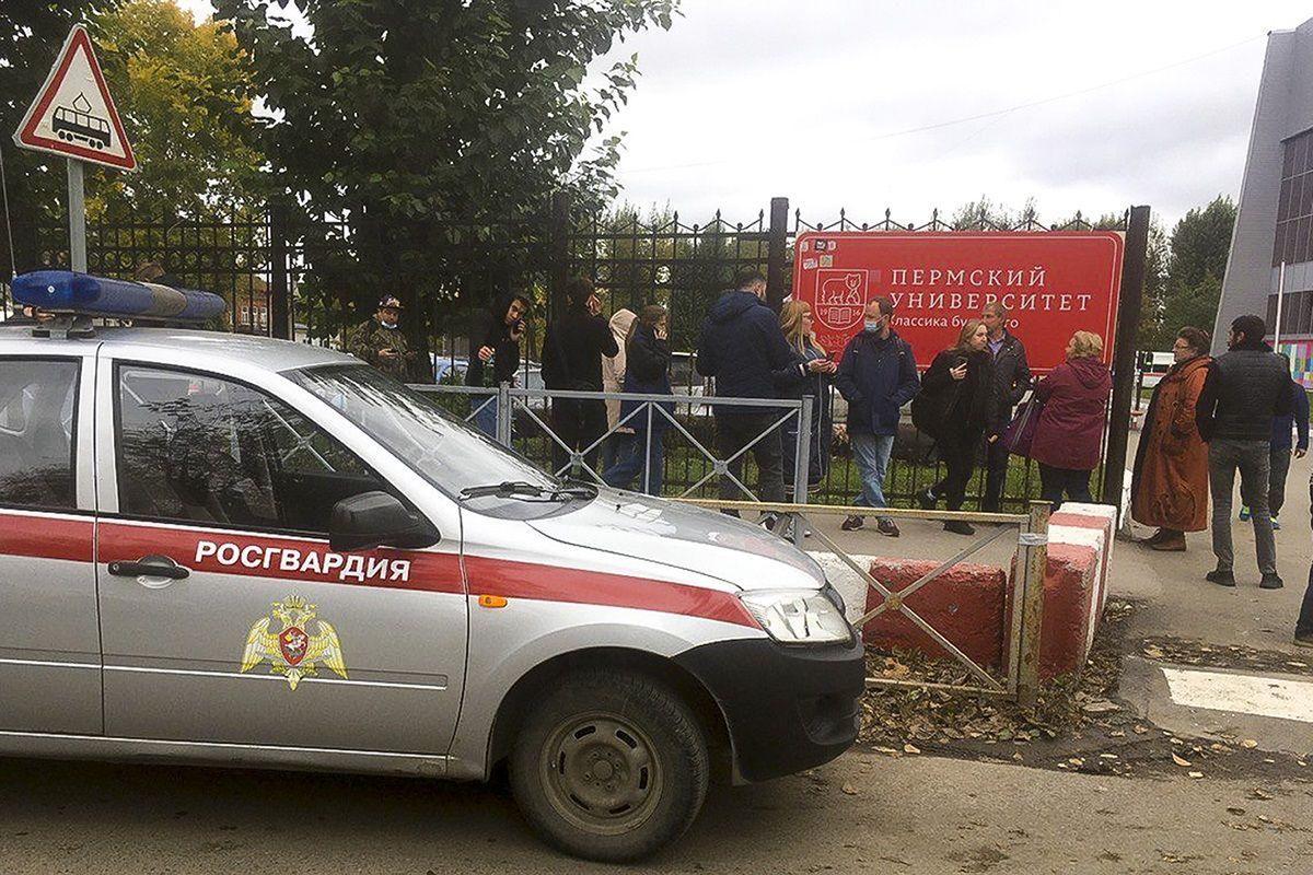 Gente tras una cerca cerca de la Universidad Estatal de Perm, con la Posguardia (Guardia Nacional) rusa a la izquierda, en Perm, Rusia, el lunes 20 de septiembre de 2021. Varias personas murieron tras un tiroteo en una universidad en la ciudad rusa de Perm, según el Comité Investigador ruso.