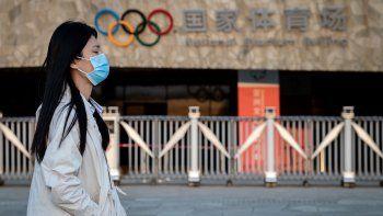 Una mujer que usa una máscara facial como medida preventiva contra el nuevo coronavirus COVID-19 camina en el parque olímpico de Beijing el 23 de marzo de 2020.