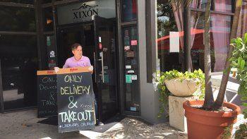 """Populares restaurantes cono Xixón, en Coral, colocan el cartel de """"solo compra y entrega a domicilio"""", mientras otros desplazan sus sillas y mesas a un lado."""