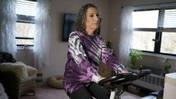 Catherine Busa se ejercita en una bicicleta estática en su casa de Nueva York el 13 de enero del 2021. Busa contrajo el COVID-19 y sobrevivió, pero ocho meses después sigue sintiendo algunos síntomas.
