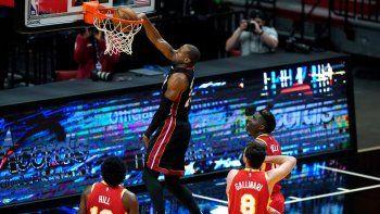 Andre Iguodala, del Heat de Miami, clava el balón ante tres jugadores de los Hawks de Atlanta en la primera mitad del encuentro del domingo 28 de febrero de 2021, en Miami.