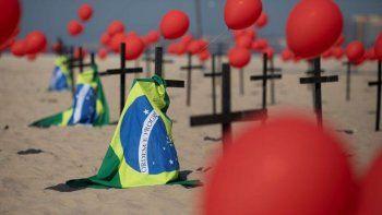 Cruces, globos rojos y la bandera de Brasil son colocados en la playa de Copacabana por el organismo no gubernamental Río de Paz en honor a las víctimas de COVID-19, en Río de Janeiro, Brasil, el sábado 8 de agosto de 2020.
