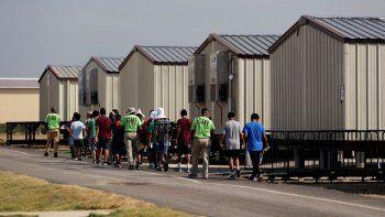 Miembros del personal escoltan a unos menores a una clase en un centro de detención para niños migrantes del gobierno de Estados Unidos en Carrizo Springs, Texas.