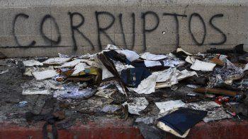 Escombros yacen frente a un grafiti el domingo 22 de noviembre de 2020 afuera del edificio del Congreso que resultó dañado durante unas protestas en la Ciudad de Guatemala