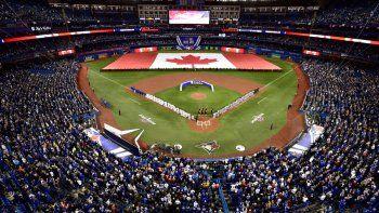 En imagen de archivo del jueves 28 de marzo de 2019, las alineaciones de los Azulejos de Toronto y los Tigres de Detroit se preparan para el inicio de un partido en el Rogers Centre de Toronto