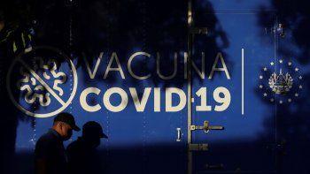 Un conductor pasa junto a un camión refrigerado del Ministerio de Salud que transporta dosis de vacunas para el COVID-19 que el gobierno de El Salvador donó a Honduras antes de partir de San Salvador, El Salvador, el jueves 13 de mayo de 2021.