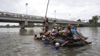 En esta fotografía de archivo del 20 de octubre de 2018, un grupo de migrantes cruza el río Suchiate en una balsa hecha de neumáticos y tablones, en la frontera entre México y Guatemala.