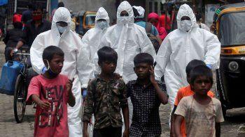 En esta fotografía de archivo del viernes 10 de julio de 2020, personal médico con ropa de protección llegan para examinar a personas que pudieran tener tener síntomas de COVID-19 en un barrio pobre en Mumbai, India.