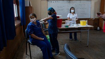 Una maestra recibe la primera dosis de la vacuna CoronaVac para COVID-19, de la china Sinovac Biotech, en la escuela pública Salvador Sanfuentes durante el inicio de la inmunización a los educadores en Santiago de Chile, el lunes 15 de febrero de 2021. El gobierno apunta a vacunar maestros y trabajadores administrativos escolares en todo el país antes del inicio del año escolar el 1 de marzo.