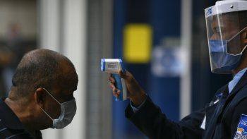 Un hombre se somete a un control de temperatura, instalado como medida para frenar el coronavirus COVID-19, a la entrada del centro comercial en Caracas, Venezuela.