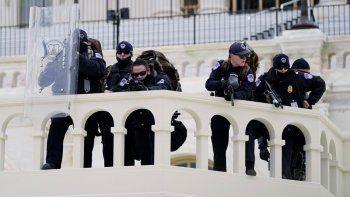 Agentes de la policía observan a unos manifestantes que tratan de pasar a través de una barrera de la policía, el miércoles 6 de enero de 2021, en el Capitolio, en Washington.