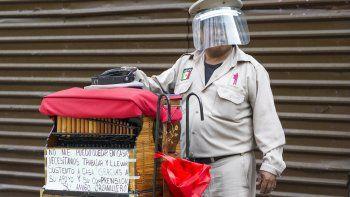 Un organillero que porta una careta protectora contra el coronavirus pide cooperación a transeúntes el sábado 16 de mayo de 2020, en la Ciudad de México.