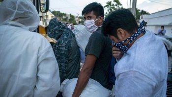 Guatemaltecos deportados por Estados Unidos, usando mascarillas para prevenir el coronavirus, abordan un autobús tras llegar al Aeropuerto La Aurora, en Ciudad de Guatemala, el 9 de junio de 2020