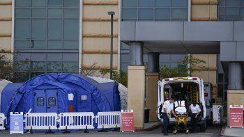 Fotografía del jueves 17 de diciembre de 2020 de trabajadores médicos retirando una camilla de una ambulancia cerca de carpas médicas erigidas afuera de la sala de emergencias del UCI Medical Center en Irvine, California.