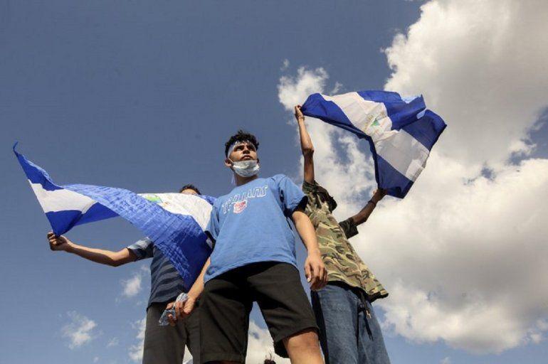 Tres jóvenes ondean banderas nacionales durante una protesta para exigir que el gobierno libere a cientos de manifestantes detenidos