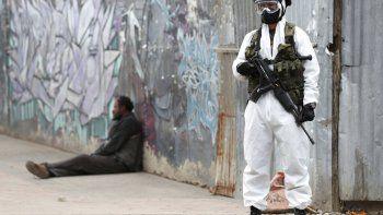 En esta imagen, tomada el 13 de julio de 2020, un soldado vestido con un equipo de protección por la pandemia del coronavirus hace guardia en Ciudad Bolívar, una zona con un elevado número de casos de COVID-19 en Bogotá, Colombia.