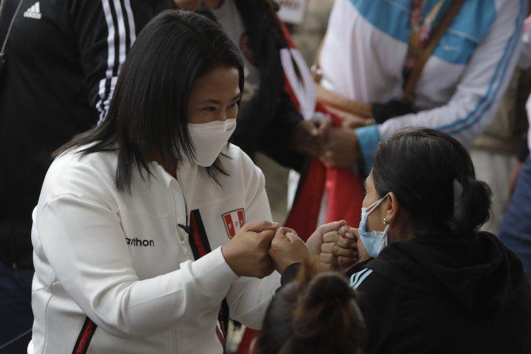 La candidata presidencial Keiko Fujimori saluda a una mujer a su llegada para desayunar con simpatizantes en Lima