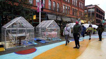 Personas caminan frente a mesas para comensales cubiertas con plástico como protección contra el coronavirus el domingo 18 de octubre de 2020, en Fulton Market, Chicago.