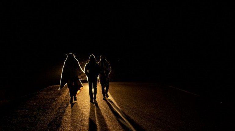 El migrante venezolano Rubi Alexander G. (L) y amigos caminan bajo temperaturas frías de noche por la carretera que une Colchane con Iquique