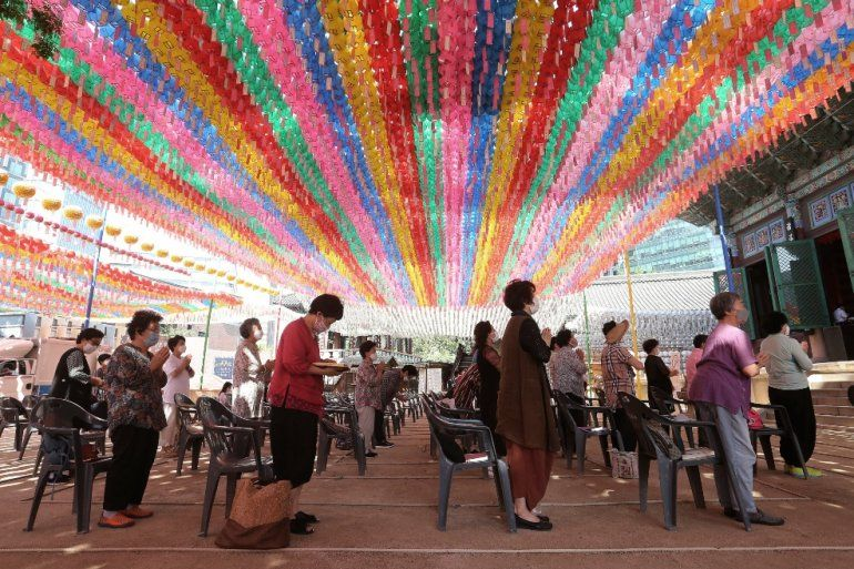 Gente con mascarillas para combatir el nuevo coronavirus reza mientras mantiene el distanciamiento social