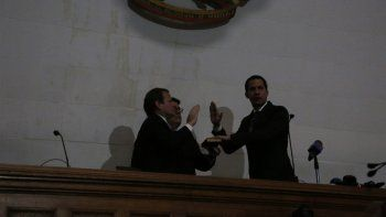 Sin energía eléctrica, el líder de la oposición Juan Guaidó, a la derecha, es juramentado como presidente de la Asamblea Nacional por el legislador Juan Pablo Guanipa en Caracas, Venezuela, el martes 7 de enero de 2020.