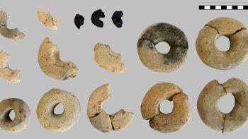 Se muestran 12 de los 14 anillos hechos de arcilla, así como los anillos orgánicos carbonizados que son el foco de esta contribución. Unidades de barra de escala: centímetros.