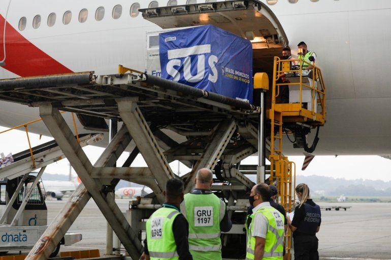 Un contenedor con vacunas contra el COVID-19 fabricadas por Oxford/AstraZeneca es bajado del avión a su llegada procedente de India en el aeropuerto internacional en Sao Paulo