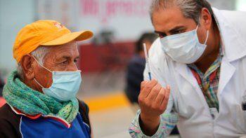 Uno de los enfermeros mexicanos muestra a un anciano una jeringa preparada con una dosis de la vacuna de Sinovac contra el coronavirus antes de aplicársela en el puesto de inoculación instalado en el Centro Cultural y Deportivo Las Américas, en Ecatepec, Estado de México, el sábado 3 de abril de 2021.