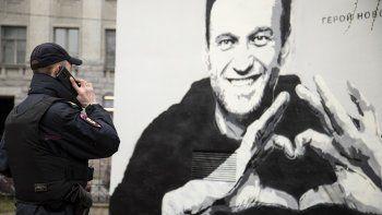 Un agente de policía habla por teléfono cerca de un grafiti con la imagen del encarcelado líder opositor ruso Alexei Navalny, en San Petersburgo, Rusia, el 28 de abril de 2021.