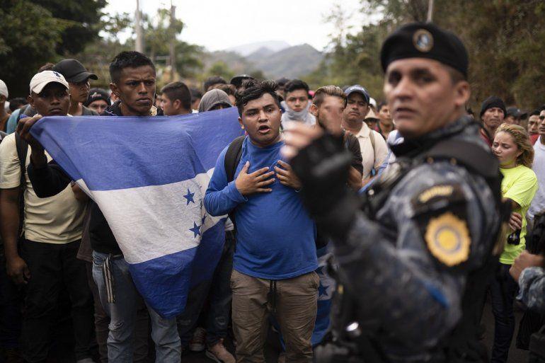 Migrantes hondureños que viajan en grupo se paran ante un policía guatemalteco