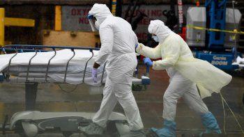 Personal médico traslada a un paciente fallecido a una morgue provisional en el Brooklyn Hospital Center, el 9 de abril de 2020 en la ciudad de Nueva York.